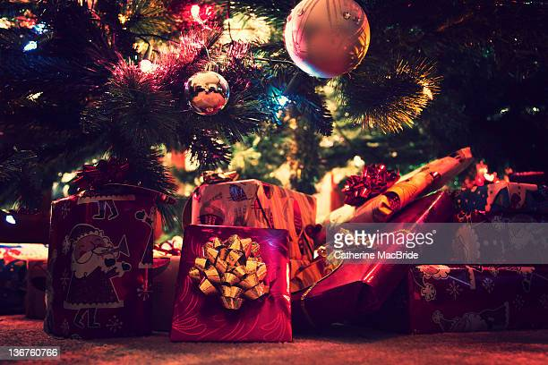 brightly wrapped christmas presents - catherine macbride stock photos and pictures