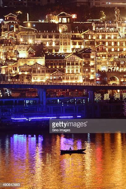 Brightly-lit buildings along Jialing River in Hongya Cave