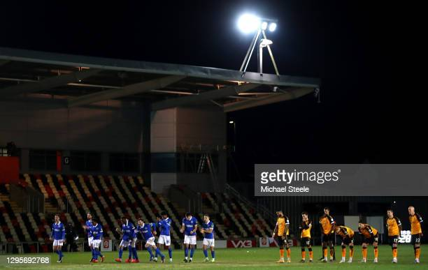 Brighton and Hove Albion players celebrate after the winning penalty was scored in the shootout as Newport County players look dejected during the FA...
