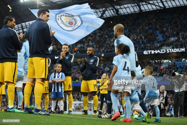 Brighton and Hove Albion players create a guard of honour for Manchester City as Vincent Kompany of Manchester City leads out his team with his...