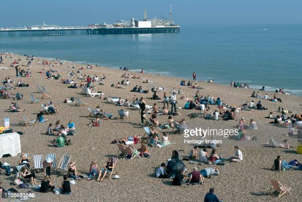 Brighton East Sussex UK 21/5/10 Sunbathers and sun worshippers on the pebbly beach with Brighton Pier in the background East Sussex England UK Artist...