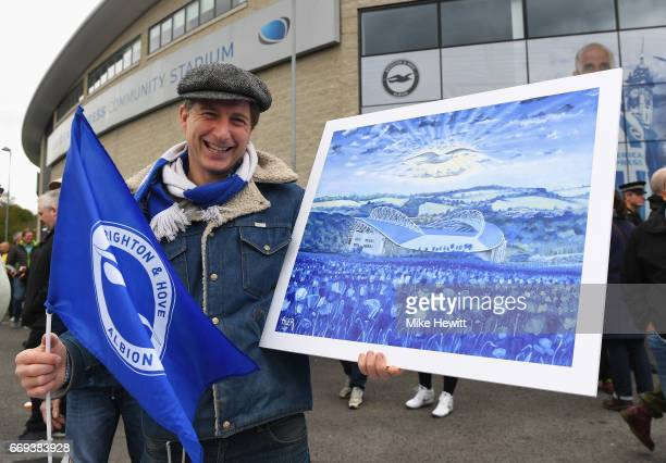 Brighton fan displays a painting of the ground prior to the Sky Bet Championship match between Brighton and Hove Albion and Wigan Athletic at Amex...