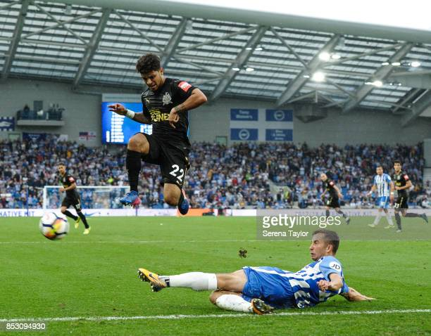 Brighton Hove Albion Defender Markus Suttner slides across the grass to kick the ball away as DeAndre Yedlin of Newcastle Untited jumps in the air...