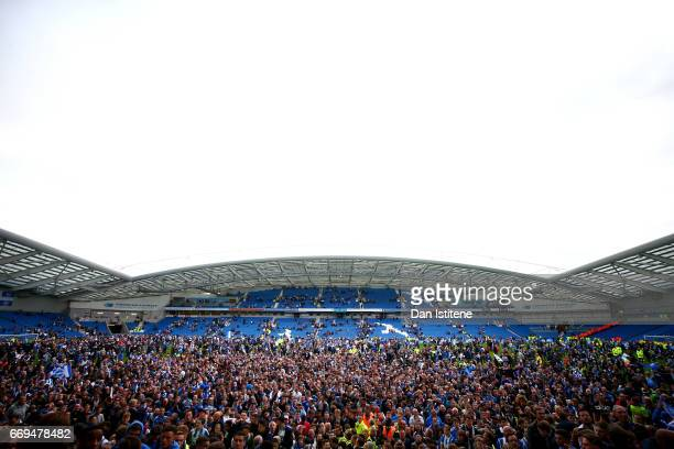 Brighton Hove Albion fans celebrate on the pitch after their team's victory in the Sky Bet Championship match between Brighton Hove Albion and Wigan...