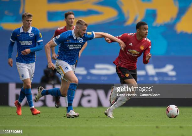 Brighton Hove Albion's Adam Webster vies for possession with Manchester United's Mason Greenwood during the Premier League match between Brighton...