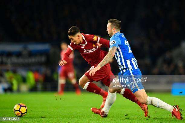 Brighton Irish defender Shane Duffy challengers Liverpool's Brazilian midfielder Roberto Firmino during the English Premier League football match...