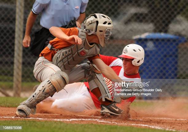 Brighton Modogs infielder Trent Swanson slides into home plate safely under the tag of Mountain View catcher Colton Sale on a fielders choice during...