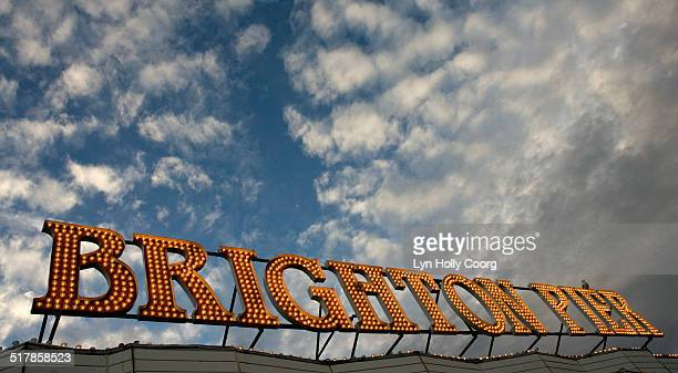 brighton pier sign in lights against cloudy sky - lyn holly coorg stock pictures, royalty-free photos & images