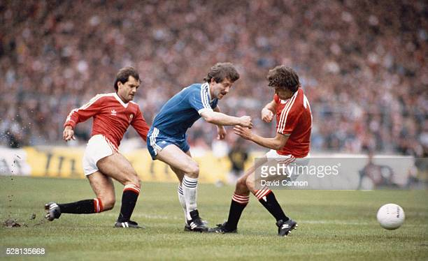 Brighton player Jimmy Case is tackled by Ray Wilkins and Bryan Robson of Manchester United during the 1983 FA Cup Final at Wembley Stadium on May 21...