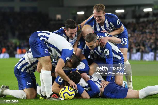 Brighton players celebrate by mobbing goalscorer Davy Propper after he scores their 2nd goal during the Premier League match between Brighton Hove...