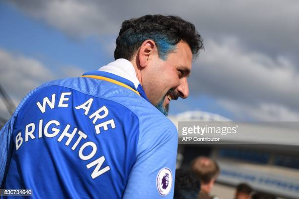 A Brighton supporter arrives for their first Premier league game the English Premier League football match between Brighton and Hove Albion and...