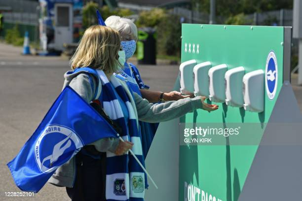 Brighton supporters wearing face coverings use the hand sanitiser provided outside as they arrive ahead of the pre-season friendly football match...