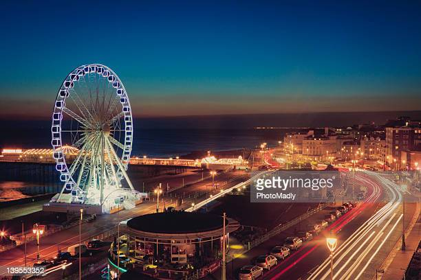 brighton wheel and seafront lit up at night - brighton stock photos and pictures