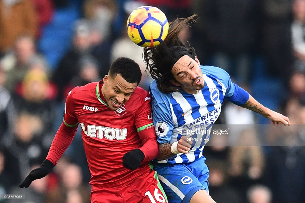 TOPSHOT - Brighton's Argentine-born Italian defender Ezequiel Schelotto (R) vies with Swansea City's Swedish defender Martin Olsson during the English Premier League football match between Brighton and Hove Albion and Swansea City at the American Express Community Stadium in Brighton, southern England on February 24, 2018. / AFP PHOTO / Glyn KIRK / RESTRICTED TO EDITORIAL USE. No use with unauthorized audio, video, data, fixture lists, club/league logos or 'live' services. Online in-match use limited to 75 images, no video emulation. No use in betting, games or single club/league/player publications. /
