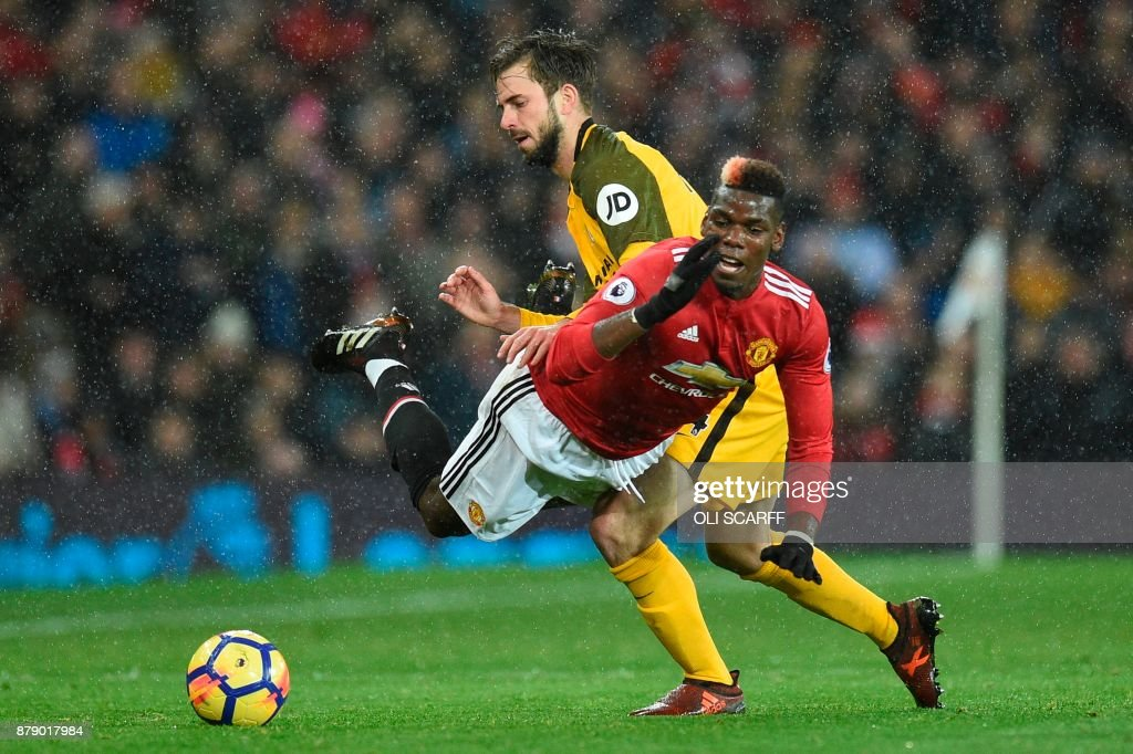 Brighton's Dutch midfielder Davy Propper (L) tackles Manchester United's French midfielder Paul Pogba (R) during the English Premier League football match between Manchester United and Brighton and Hove Albion at Old Trafford in Manchester, north west England, on November 25, 2017. / AFP PHOTO / Oli SCARFF / RESTRICTED TO EDITORIAL USE. No use with unauthorized audio, video, data, fixture lists, club/league logos or 'live' services. Online in-match use limited to 75 images, no video emulation. No use in betting, games or single club/league/player publications. /