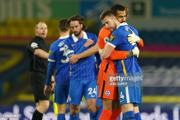 Brighton's English defender Adam Webster embraces Brighton's Spanish goalkeeper Robert Sanchez as Brighton celebrate their win on the pitch after the...