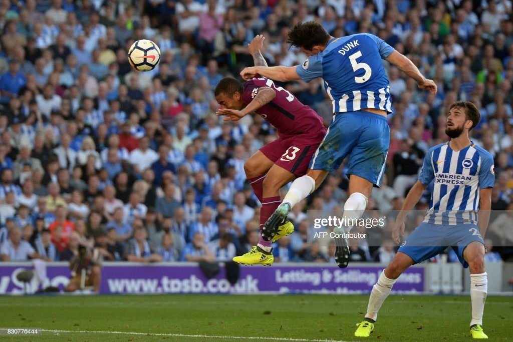Brighton's English defender Lewis Dunk (2nd R) heads the ball into his own net under pressure from Manchester City's Brazilian striker Gabriel Jesus (L) during the English Premier League football match between Brighton and Hove Albion and Manchester City at the American Express Community Stadium in Brighton, southern England on August 12, 2017. / AFP PHOTO / CHRIS J RATCLIFFE / RESTRICTED TO EDITORIAL USE. No use with unauthorized audio, video, data, fixture lists, club/league logos or 'live' services. Online in-match use limited to 75 images, no video emulation. No use in betting, games or single club/league/player publications. /