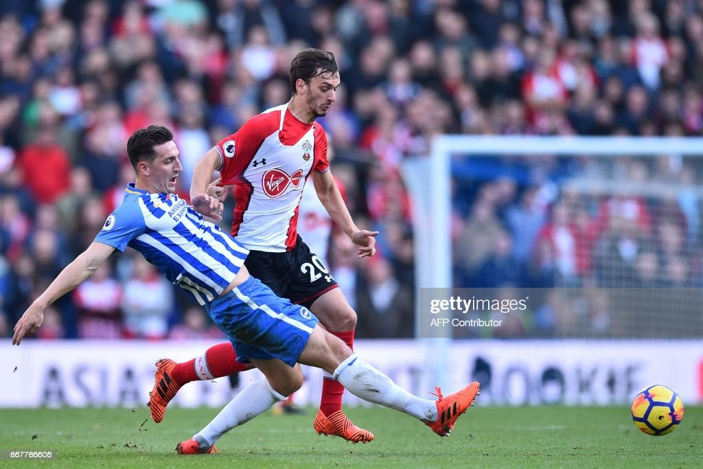 Brighton's English defender Lewis Dunk (L) tackles Southampton's Italian striker Manolo Gabbiadini during the English Premier League football match between Brighton and Hove Albion and Southampton at the American Express Community Stadium in Brighton, southern England on October 29, 2017. / AFP PHOTO / Glyn KIRK / RESTRICTED TO EDITORIAL USE. No use with unauthorized audio, video, data, fixture lists, club/league logos or 'live' services. Online in-match use limited to 75 images, no video emulation. No use in betting, games or single club/league/player publications. /