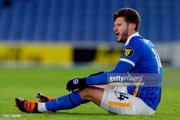 Brighton's English midfielder Adam Lallana sits on the pitch during the English Premier League football match between Brighton and Hove Albion and...