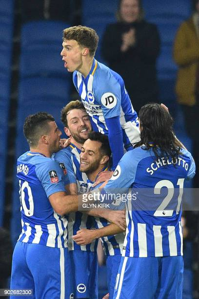 Brighton's English midfielder Dale Stephens celebrates with teammates scoring the team's first goal during the English FA Cup third round football...