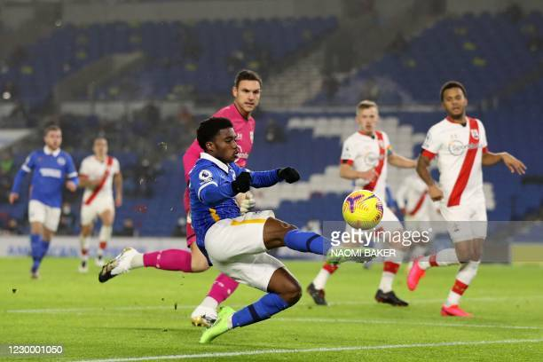 Brighton's English midfielder Tariq Lamptey stretches for the ball in front of Southampton's English goalkeeper Alex McCarthy during the English...