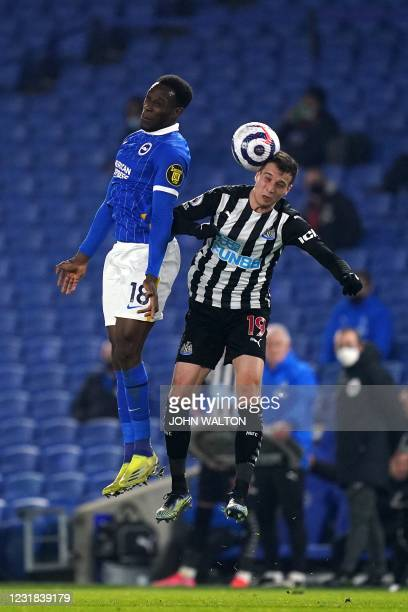Brighton's English striker Danny Welbeck and Newcastle United's Spanish midfielder Javier Manquillo jump up for the ball during the English Premier...