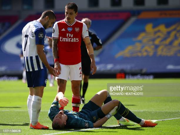 Brighton's French striker Neal Maupay looks on as Arsenal's German goalkeeper Bernd Leno lays injured during the English Premier League football...