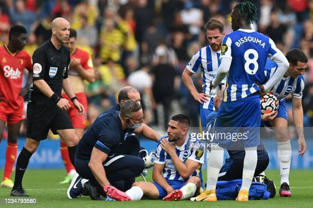 Brighton's French striker Neal Maupay receives medical attention after hurting his shoulder in a challenge during the English Premier League football...