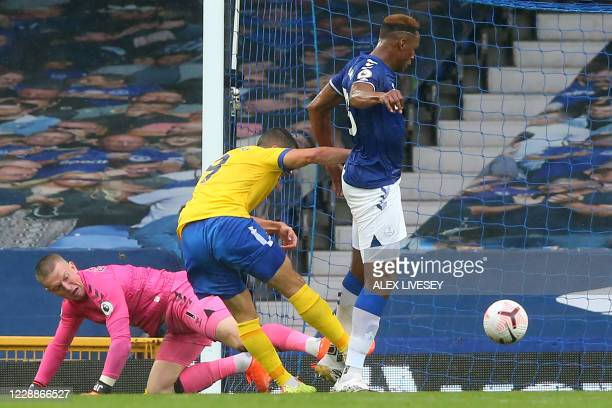 Brighton's French striker Neal Maupay shoots to score their first goal following a mistake from Everton's English goalkeeper Jordan Pickford during...