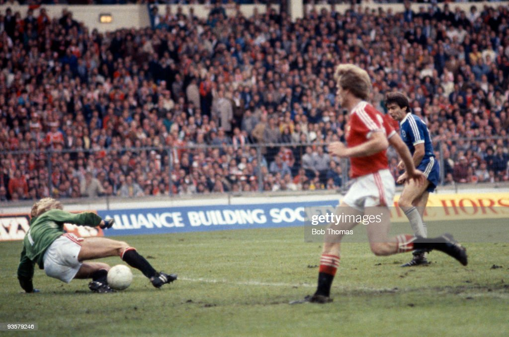 Brighton's Gordon Smith (blue shirt - right) is foiled by Manchester United goalkeeper, Gary Bailey (left) in the last four minutes of extra time during the FA Cup Final between Brighton and Manchester United held at Wembley Stadium, London on 21st May 1983. The teams were still drawn 2-2 after extra time. Manchester United won the replay 4-0. (Photo by Bob Thomas/Getty Images).