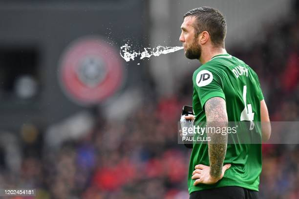 Brighton's Irish defender Shane Duffy spits out some water during a break in play in the English Premier League football match between Sheffield...