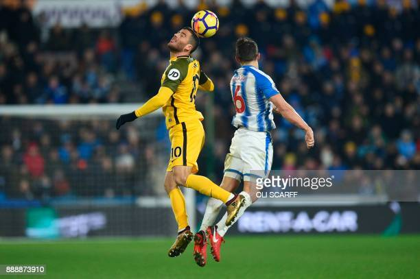 Brighton's Israeli striker Tomer Hemed wins the ball in the air from Huddersfield Town's English midfielder Jonathan Hogg during the English Premier...