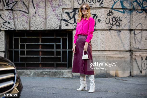 Brigita Daisy is seen wearing boredeaux leather skirt, pink silk shirts, slouchy white boots, mini Jacquemus bag outside the Ferragamo show during...
