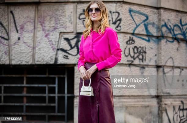 Brigita Daisy is seen wearing boredeaux leather skirt, pink silk shirts, white mini Jacquemus bag outside the Ferragamo show during Milan Fashion...