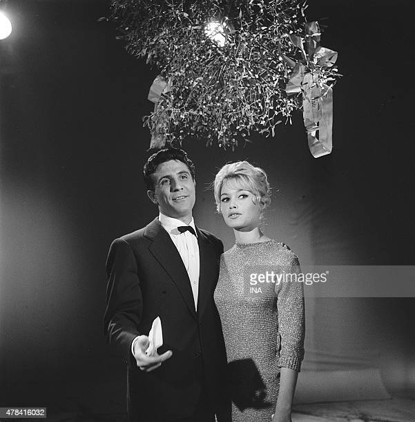 Brigitte Bardot and Gilbert Becaud under a bouquet of mistletoe present their wishes for year 1958 during the shooting of the program Parade of the...