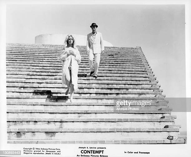 Brigitte Bardot and Michel Piccoli walking down stairs in a scene from the film 'Contempt', 1963.