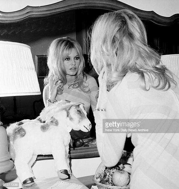 Brigitte Bardot checks her appearance in mirror at the Plaza Hotel. A doctor ordered dark glasses to protect her right eye, irritated by flashbulbs.