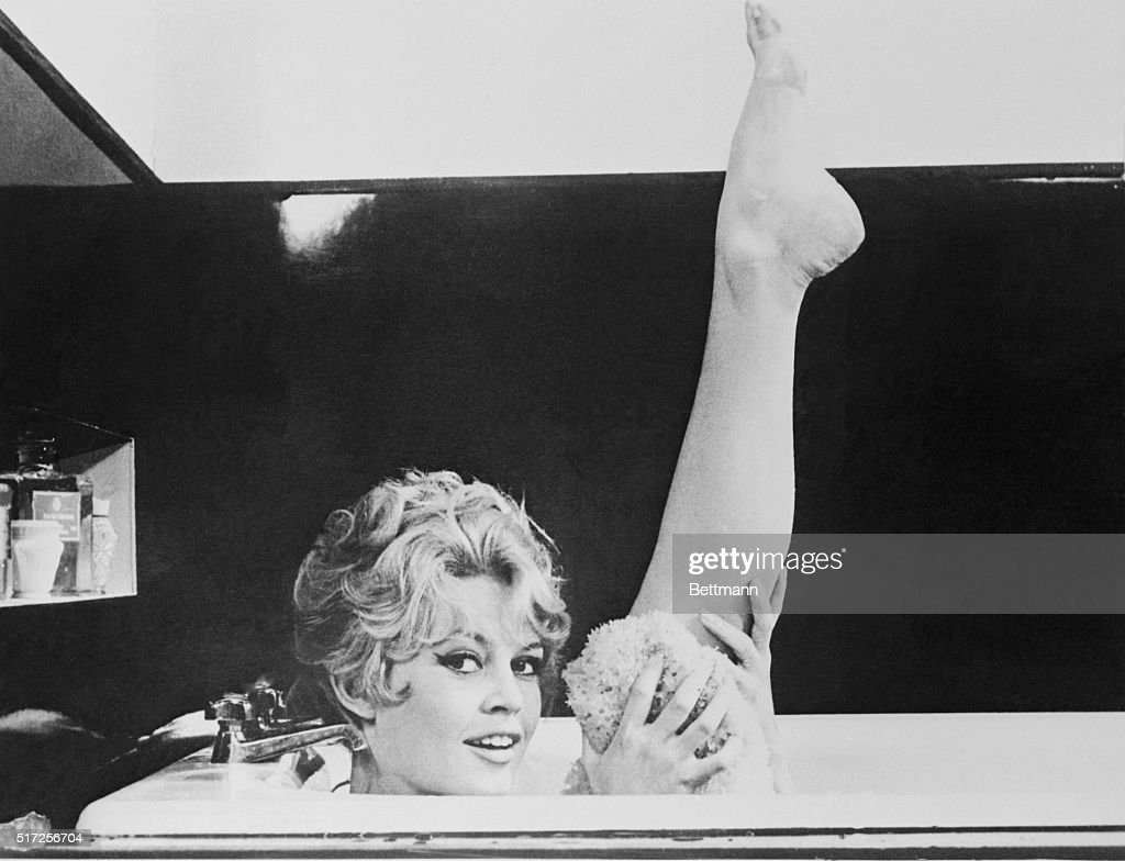 Brigitte Bardot holding up leg in bathtub in the 1957 film Une Parisienne.