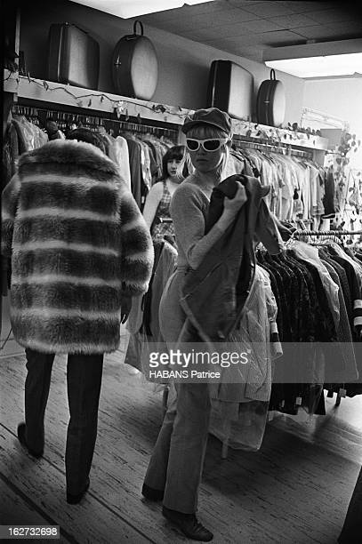 Brigitte Bardot In The United States Brigitte BARDOT dans une boutique de vêtements à Los Angeles Essayage d'un manteau de fourrure avec son...