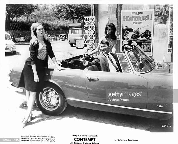 Brigitte Bardot leaning against car as Jack Palance looks over to her in a scene from the film 'Contempt' 1963