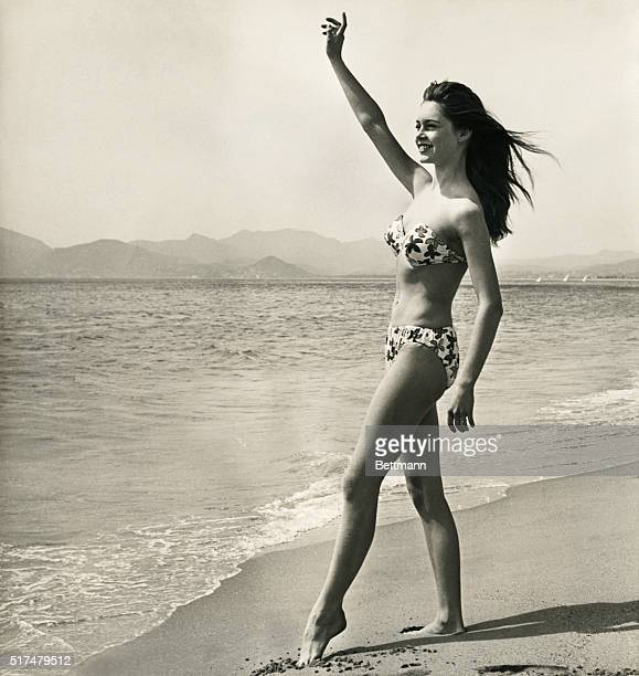 Brigitte Bardot playing the role of Javotte Lemoine waves from the shore in a scene from the 1952 French comedy Le Trou Normand