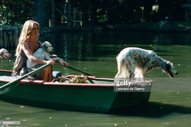 Brigitte Bardot with her dogs on the pond at her home in Bazoches