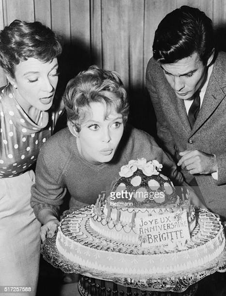 Brigitte Bardot young French screen actress who has risen meteorically to stardom is shown getting ready for the big blow out of candles on a...