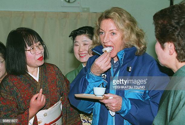 Brigitte Fisk chief coach of the Italian luge team tastes a traditional Japanee confectionery following the flag raising ceremony for the Italian...