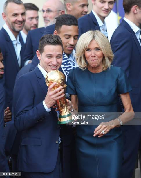 Brigitte Macron and Florian Thauvin hold up the World Cup trophy as French President Emmanuel Macron receives France's national football team At...