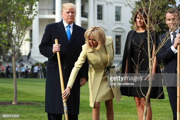Brigitte Macron reaches over to touch US President Donald Trump's shovel during a tree planting ceremony with US first lady Melania Trump and French...