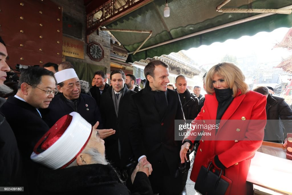 Brigitte Macron (front R-red coat), wife of French President Emmanuel Macron (C), shakes hands with an elderly iman during a visit to the Great Mosque of Xian in the northern Chinese city of Xian on January 8, 2018. Macron on January 8 launched a state visit to China in Xian -- the starting point of the ancient Silk Road -- in a nod to his counterpart's scheme to revive the famous trading route. / AFP PHOTO / POOL / ludovic MARIN