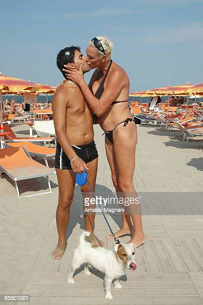 Brigitte Nielsen and her husband Mattia Dessi kiss on the beach as they walk their dog Jooker on July 29 2005 in Cervia Italy