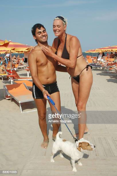 Brigitte Nielsen and her husband Mattia Dessi walk on the beach with their dog Jooker on July 29 2005 in Cervia Italy