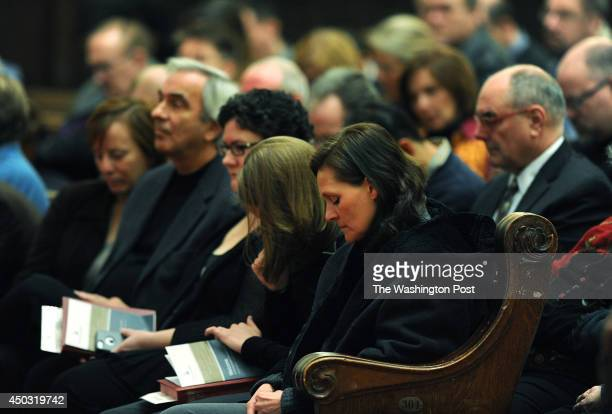 Brigitte Schaefer center lowers her head in prayer as she attends a service at Foundry United Methodist Church on Sunday January 26 2014 in...